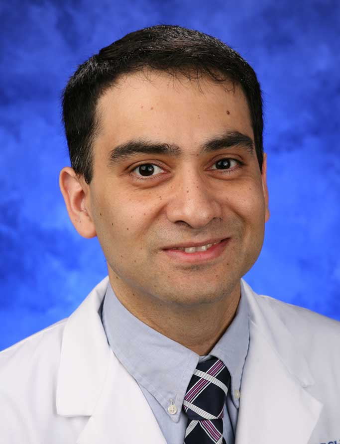 A portrait photograph of Dr. Aditya Joshi in front of a professional photo background.