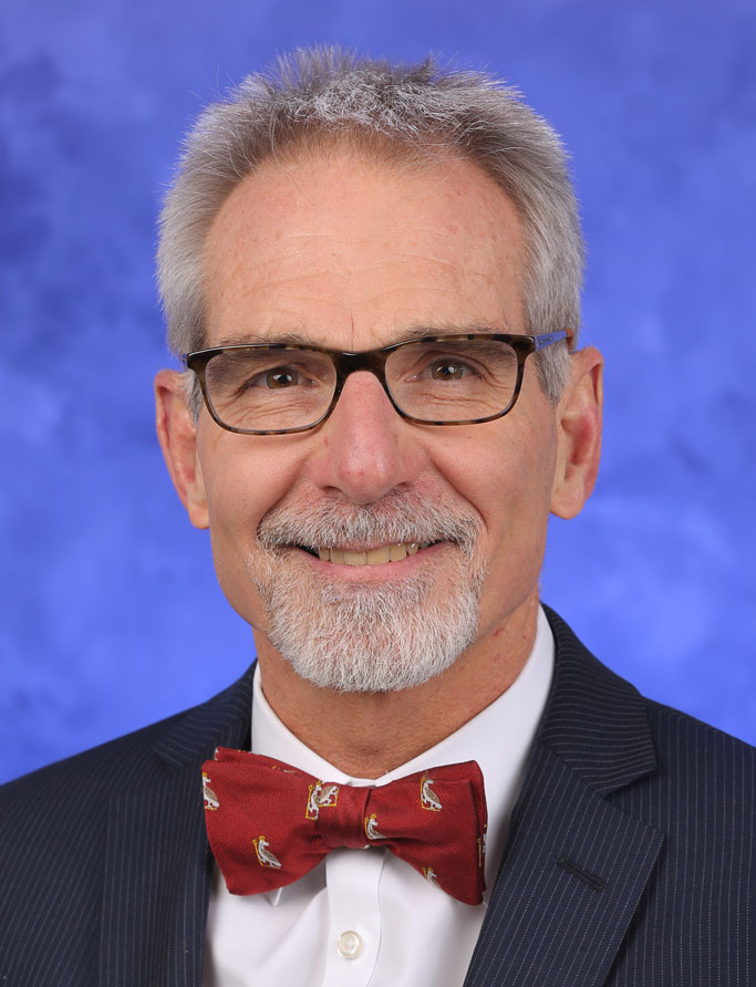 Berend Mets, MBChB, PhD, FRCA, FFA(SA), is Chair of the Department of Anesthesiology and Perioperative Medicine at Penn State College of Medicine. He is pictured in a dress shirt, bowtie and suit coat against a blue background.