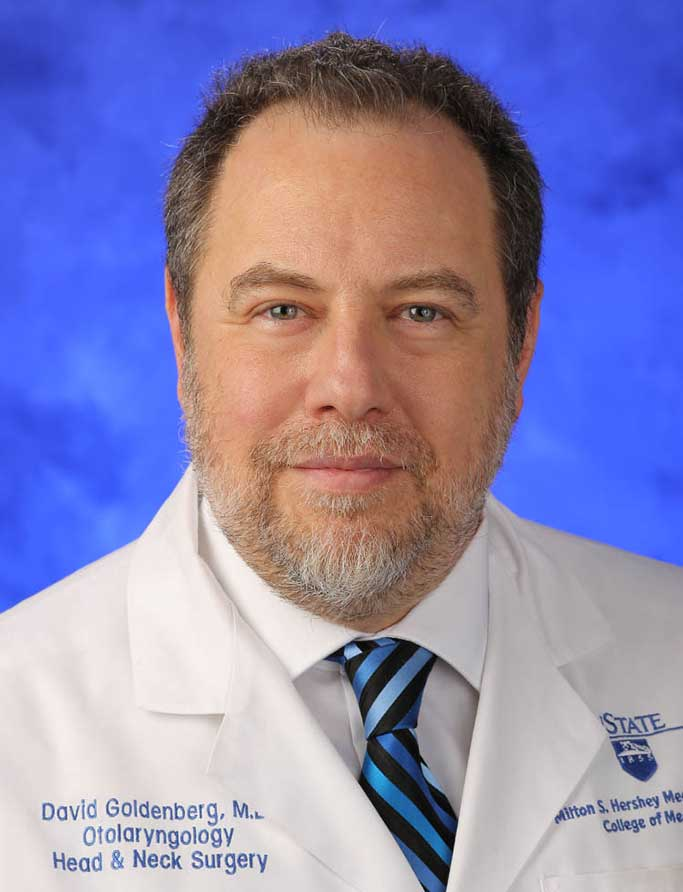 David Goldenberg, MD, FACS, is the Chair, Department of Otolaryngology - Head and Neck Surgery; Steven and Sharon Baron Professor at Penn State College of Medicine. He is pictured in a white medical coat against a blue background.