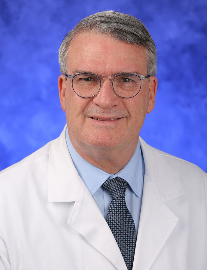 Donald Mackay, MD, is Interim Chair of the Department of Surgery at Penn State College of Medicine. He is pictured in a dress shirt, tie and medical coat against a professional photo background.