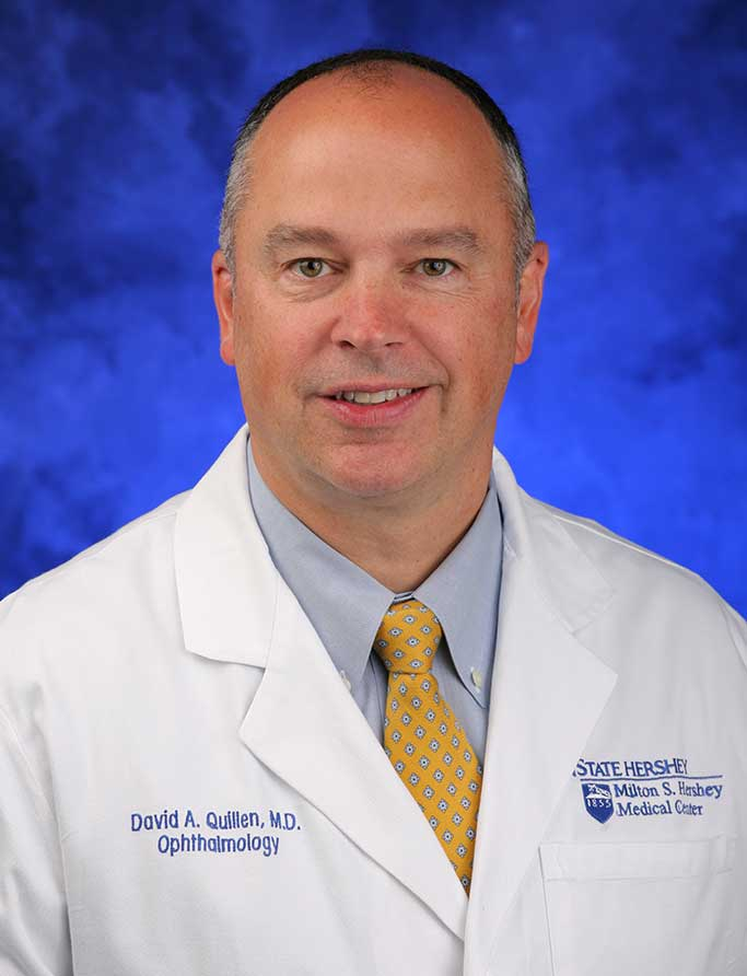David Quillen, MD, is Chair of the Department of Ophthalmology at Penn State College of Medicine. He is pictured in a dress shirt, tie and medical coat against a blue background.