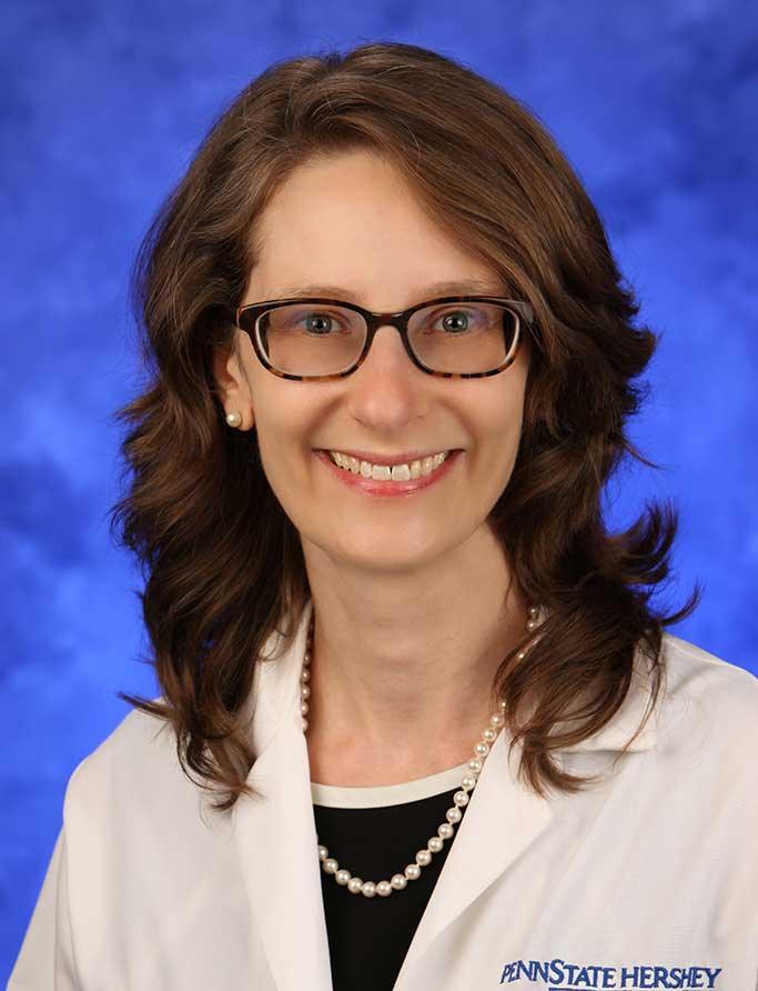 Erika Saunders, MD, is Chair of the Department of Psychiatry and Behavioral Health at Penn State College of Medicine. She is pictured in a dress shirt and medical coat against a blue background.