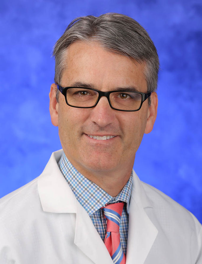 A head-and-shoulders professional photo of Dr. Jeffrey Miller in a medical coat, shirt and tie on a professional photo background.