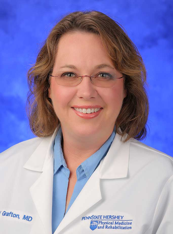 Lori Grafton, MD, is Interim Chair of the Department of Physical Medicine and Rehabilitation at Penn State College of Medicine. She is pictured in a blue dress shirt and white medical coat against a blue background.