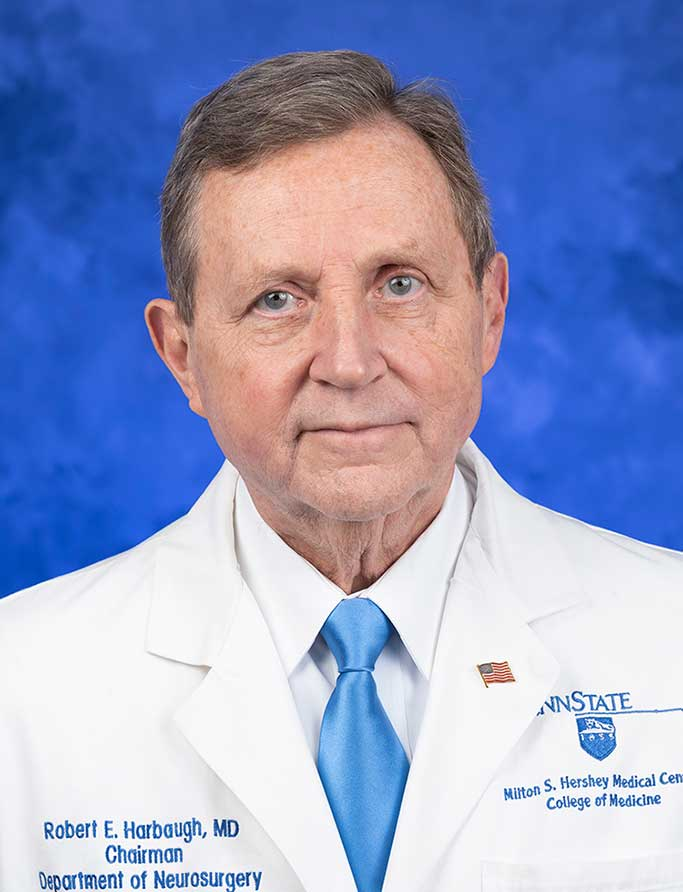 Robert E. Harbaugh, MD, FACS, FAHA, is Chair of the Department of Neurosurgery at Penn State College of Medicine. He is pictured in a white dress shirt, blue tie and white medical coat against a blue background.