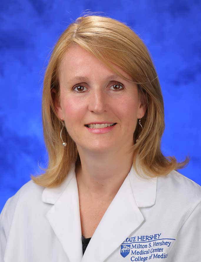 Sarah Iriana, MD, is Interim Chair of the Department of Pediatric at Penn State College of Medicine. She is pictured in a white medical coat against a blue background.